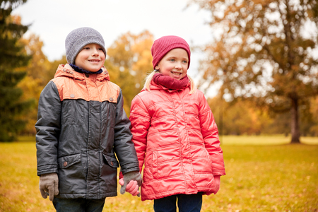 fashion boy: childhood, leisure, friendship and people concept - happy little girl and boy holding hands in autumn park