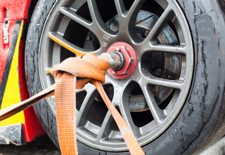 bracing: motosports, transportation and racing concept - close up of race car wheel with tow rope tied to it