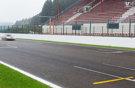rain weather: motosports, weather, extreme and race concept - close up of car driving on speedway track or road and stands under rain Stock Photo