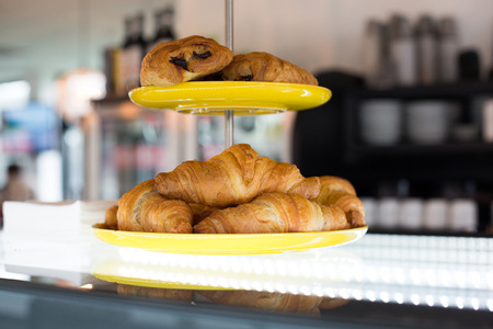 cakestand: food, baking, junk-food and unhealthy eating concept - close up of croissants and buns on cake stand at cafe or bakery Stock Photo
