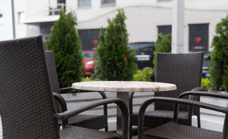 rain weather: weather, public places and season concept - table and wicker chairs on street cafe terrace under rain