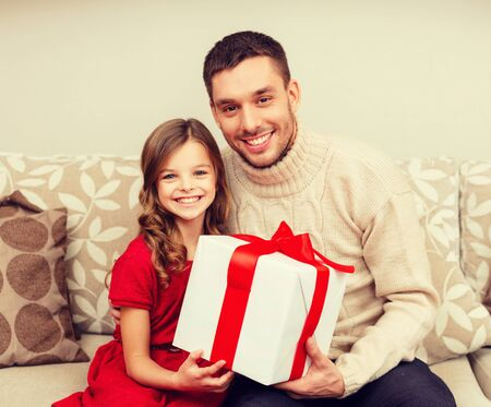 young parents: christmas, x-mas, winter, happiness and people concept - smiling father and daughter holding gift box Stock Photo