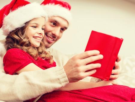 familia, la navidad, x-mas, la felicidad y el concepto de la gente - libro sonriente padre e hija en sombreros de santa ayudante de lectura