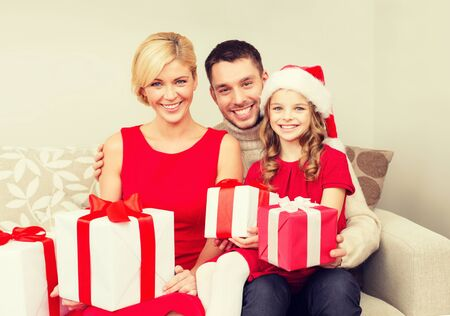 christmas winter: family, christmas, x-mas, winter, happiness and people concept - smiling family in santa helper hats with many gift boxes Stock Photo