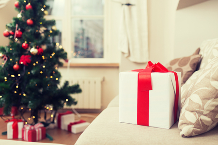 christmas tree presents: christmas, x-mas, holidays, winter and happiness concept - gift box on coach at home