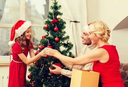 arbol genealógico: familia, la navidad, Navidad, la felicidad y el concepto de la gente - sonriendo familia en Santa helper sombreros decorar el árbol de navidad