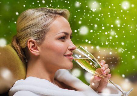 mujer sentada: la gente, la belleza, el estilo de vida, las vacaciones y el concepto de relajación - hermosa mujer joven en traje de baño blanco acostado en chaise-longue y bebiendo champán en el spa con efecto de nieve Foto de archivo