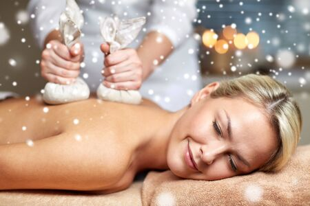massagist: people, beauty, spa, winter and relaxation concept - close up of beautiful young woman lying and having herbal bag back massage in spa salon with snow effect Stock Photo
