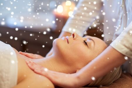 relaxation massage: people, beauty, spa, healthy lifestyle and relaxation concept - close up of beautiful young woman lying with closed eyes and having massage in spa with snow effect