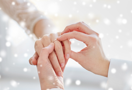 nude lesbian: people, homosexuality, same-sex marriage and love concept - close up of happy lesbian couple hands putting on wedding ring over snow effect Stock Photo