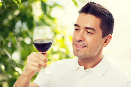 degustating: profession, drinks, leisure, holidays and people concept - happy man drinking red wine from glass over green background Stock Photo