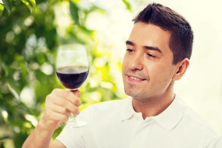 Beruf, Getränke, Freizeit, Urlaub und Menschen Konzept - happy man trinken Rotwein aus Glas über grünem Hintergrund