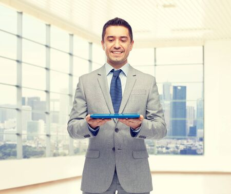 office man: business, people and technology concept - happy smiling businessman in suit holding tablet pc computer over office room background