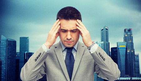 head ache: business, people, crisis and fail concept - businessman in suit having head ache over city background Stock Photo