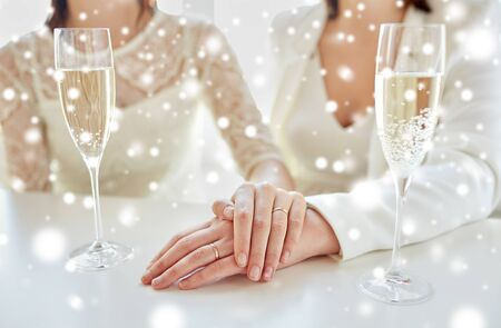 nude lesbian: people, homosexuality, same-sex marriage, celebration and love concept - close up of happy married lesbian couple hands on top and champagne glasses over snow effect Stock Photo