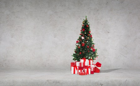 celebration, winter holidays and advertisement concept - christmas tree with gifts and santa hat over concrete wall background