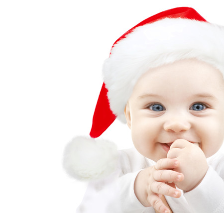 babyhood: christmas, babyhood, childhood and people concept - happy baby in santa hat over white
