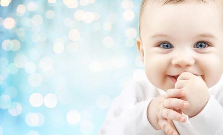 kisbabák: kisgyermekkor, a gyermekkor és az emberek koncepció - boldog baba arca fölött kék szabadság fények háttér Stock fotó