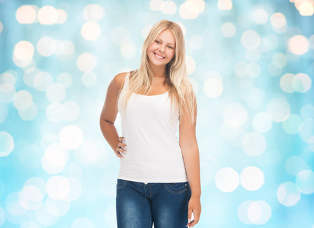 overweight students: people, holidays, style and body type concept - smiling young woman in blank white shirt and jeans over blue holidays lights background