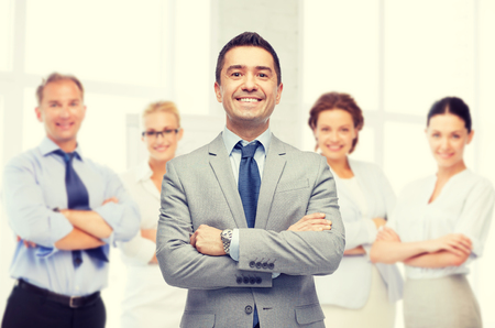 business, people and office concept - happy smiling business team over office room background Stock Photo