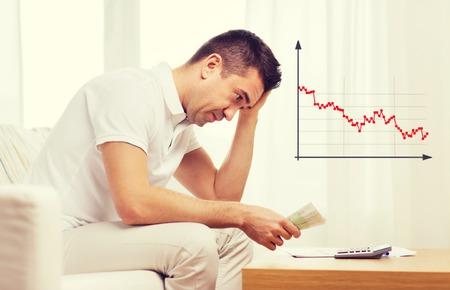 bedrijfsleven, spaargeld, de financiële crisis en de mensen concept - boos man met geld en rekenmachine thuis Stockfoto