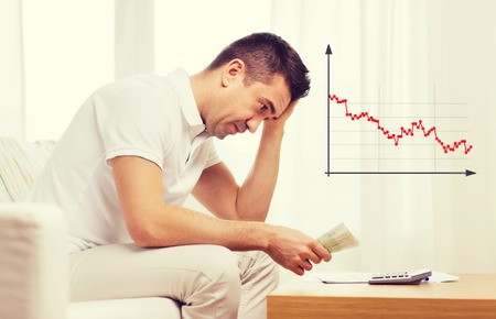 budget crisis: business, savings, financial crisis and people concept - upset man with money and calculator at home