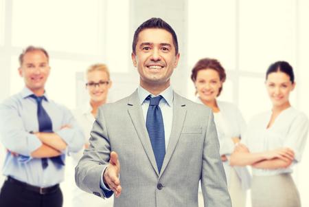 bedrijfsleven, mensen, gebaar, partnerschap en groet concept - gelukkig lachend zakenman in pak met team over kantoorruimte achtergrond schudden hand
