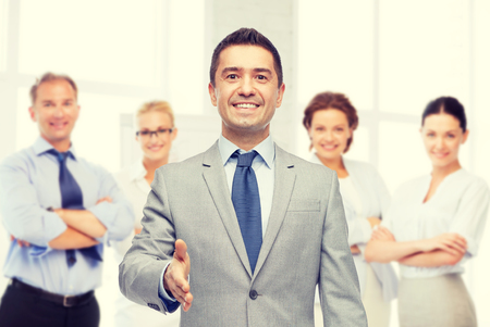Unternehmen, Menschen, Geste, Partnerschaft und Gruß-Konzept - glücklich lächelnde Geschäftsmann im Anzug mit Team über Büroraum Hintergrund die Hand schütteln