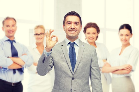 business, people, gesture and success concept - happy smiling businessman in suit with team over office room background showing ok hand sign