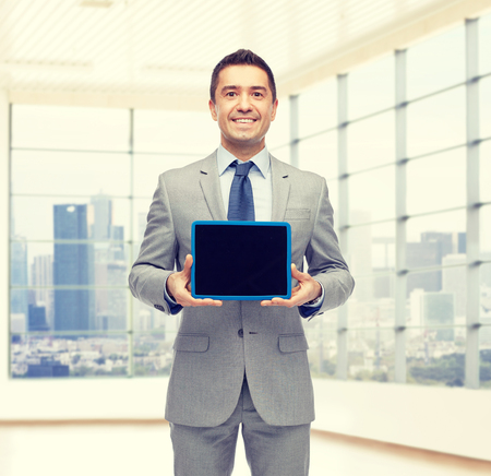 space suit: business, people and technology concept - happy smiling businessman in suit showing tablet pc computer black blank screen over city office room window background
