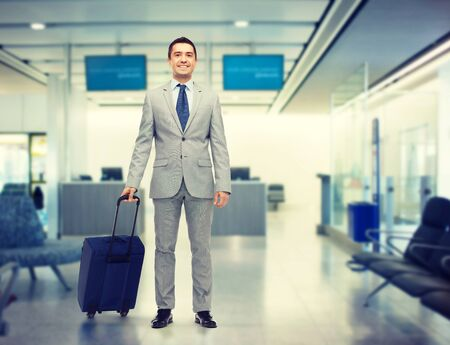 trip over: business trip, traveling, luggage and people concept - happy businessman in suit with travel bag over airport background Stock Photo