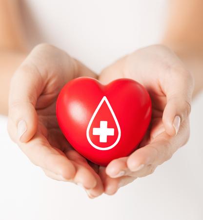 gezondheidszorg, geneeskunde en bloeddonatie concept - vrouwelijke handen met rood hart met donor teken Stockfoto