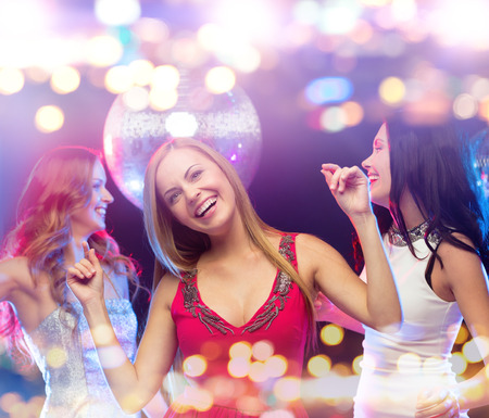 dancing club: party, celebration, holidays, nightlife and people concept - happy women dancing at night club
