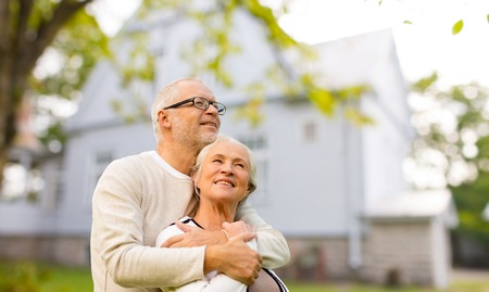 happy senior: family, age, home, real estate and people concept - happy senior couple hugging over living house background