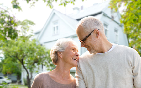 nice accommodations: family, age, home, real estate and people concept - happy senior couple hugging over living house background
