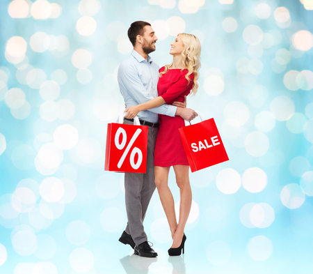 sales person: people, sale, discount and christmas concept - happy couple with red shopping bags hugging over blue holidays lights background