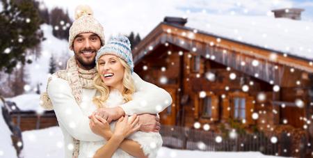casa de campo: invierno, vacaciones, pares, navidad y concepto de la gente - la sonrisa del hombre y la mujer en los sombreros y abrazos bufanda más de la casa de campo de madera y fondo de la nieve