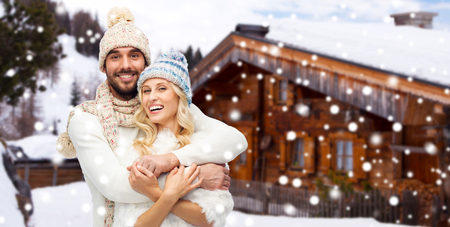 cottage: winter, vacation, couple, christmas and people concept - smiling man and woman in hats and scarf hugging over wooden country house and snow background Stock Photo