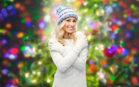 winter fashion: winter, fashion, christmas and people concept - smiling young woman in winter hat, sweater and gloves over holidays lights background