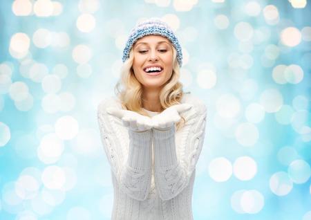 jovenes felices: invierno, anuncio, la navidad y el concepto de la gente - mujer joven y sonriente en el sombrero de invierno y suéter sosteniendo algo en sus palmas vacías durante las vacaciones luces de fondo azul