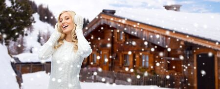 christmas winter: winter, fashion, vacation, christmas and people concept - smiling young woman in earmuffs and sweater over wooden country house and snow background
