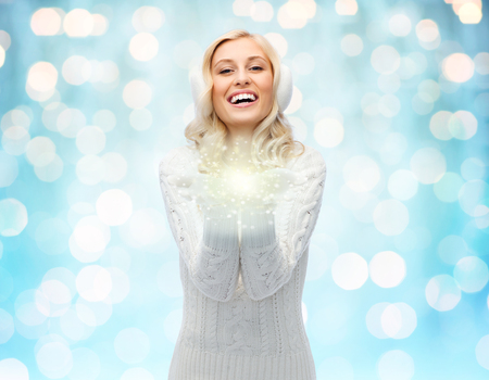 christmas light: winter, magic, christmas and people concept - smiling young woman in earmuffs and sweater holding fairy dust on palms over blue holidays lights background