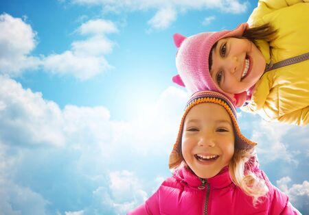 family life: childhood, leisure, friendship and people concept - happy girls faces outdoors over blue sky and clouds background Stock Photo