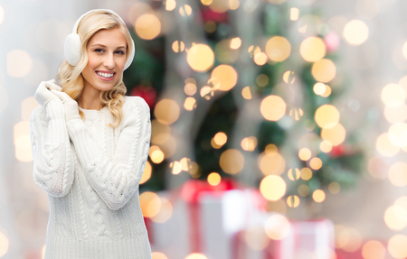 earmuffs: winter, fashion, christmas and people concept - smiling young woman in earmuffs and sweater over holidays lights background