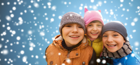 girl friend: childhood, christmas, winter, friendship and people concept - group of happy kids hugging over snow background