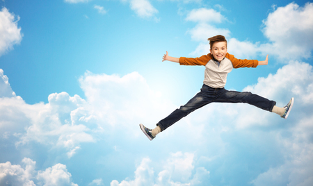 legs spread: happiness, childhood, freedom, movement and people concept - happy smiling boy jumping in air over blue sky and clouds background