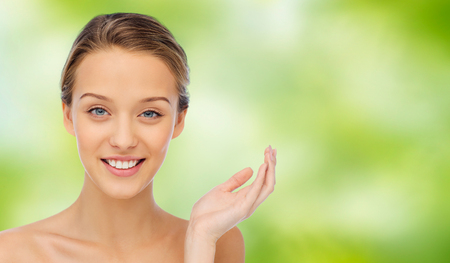 natural beauty: beauty, people and health concept - smiling young woman face and shoulders over green natural background Stock Photo