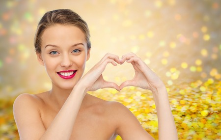 heart in hand: beauty, people, love, valentines day and make up concept - smiling young woman with pink lipstick on lips showing heart shape hand sign over golden glitter or holidays lights background