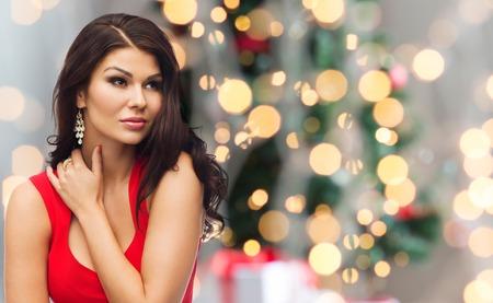 navidad elegante: personas, navidad, días de fiesta y el concepto de lujo - mujer atractiva en el vestido rojo sobre fondo de las luces