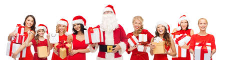 santa cap: people, holidays, christmas and celebration concept - santa calaus and happy women with gift boxes Stock Photo